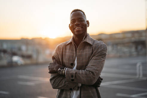 Cheerful man with arms crossed standing at parking lot during sunset - MPPF01459