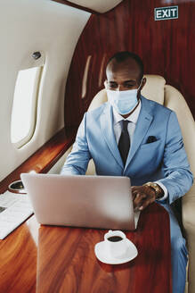Male entrepreneur working on laptop in private jet during COVID-19 - OIPF00295
