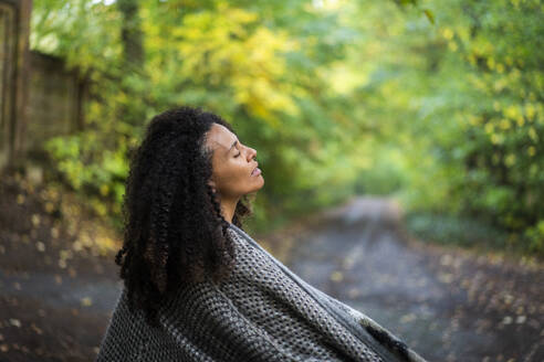 Curly hair woman wearing jacket sitting with eyes closed on footpath in forest - AKLF00003
