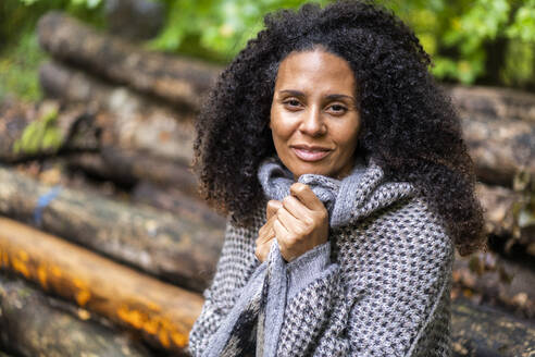 Smiling woman wearing jacket staring while sitting in forest - AKLF00006
