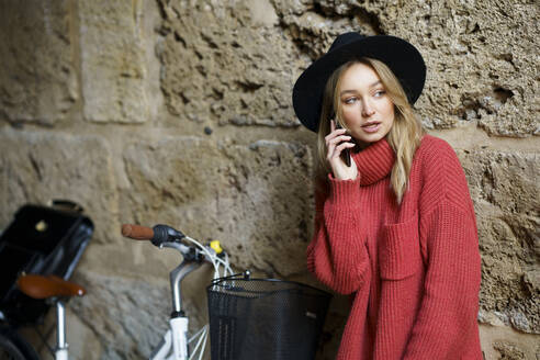 Woman wearing hat talking on mobile phone while leaning on wall by bicycle - JSMF01910