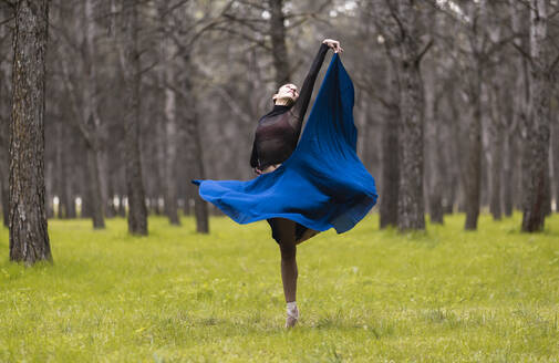 Young ballet dancer spinning while dancing in forest - JCCMF01030