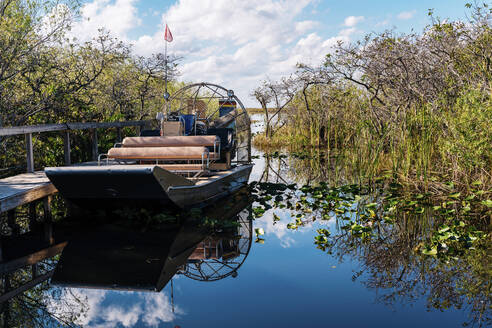 Airboat by pier in lake against sky at Everglades National Park - GEMF04612
