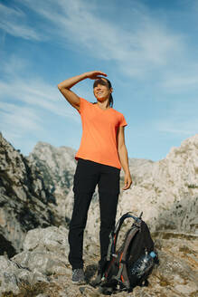 Woman shielding eyes while looking at view standing on mountain at Cares Trail in Picos De Europe National Park, Asturias, Spain - DMGF00450