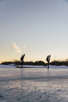 Two female figure skaters practicing together on frozen lake at dusk - RSGF00533