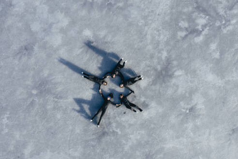 Aerial view of group of female ice-skaters lying together on surface of frozen lake - RSGF00542