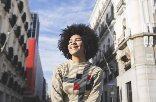 Young woman smiling while standing in city - JCCMF01074