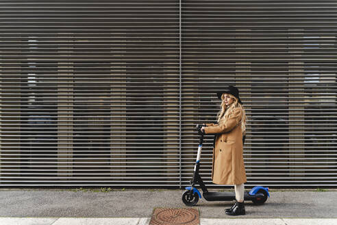 Woman with electric push scooter standing against metallic wall - FMOF01342