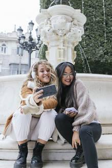 Multi-ethnic female friends taking selfie through smart phone while sitting against fountain - JRVF00209