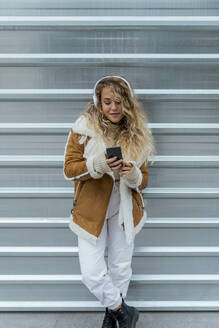 Young woman listening music through smart phone while standing against metal wall - JRVF00242