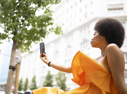 Young woman taking selfie through smart phone in city - JCCMF01145