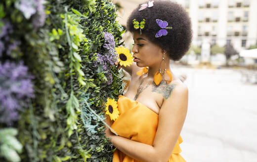 Young female hipster smelling flower outdoors - JCCMF01154