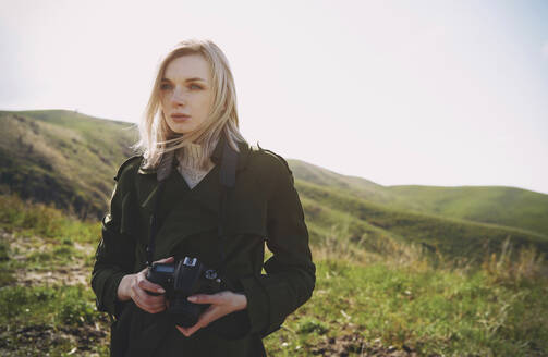 Beautiful blond woman with digital camera standing on hill against sky - AZF00140
