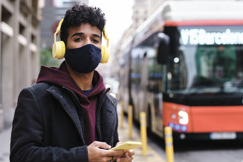 Man wearing protective face mask listening music through headphones while waiting on street in city - AGOF00002