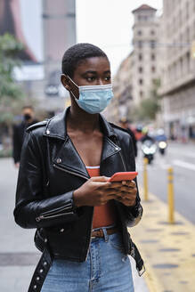 Young woman wearing protective face mask using mobile phone while standing in city - AGOF00005