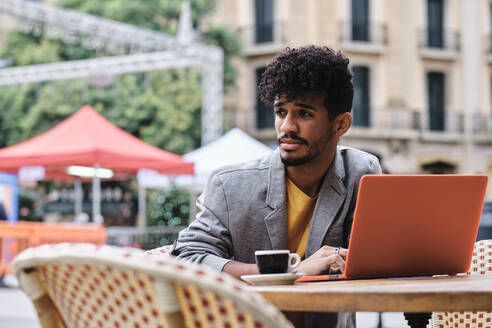 Young fashionable man with laptop looking away while sitting at sidewalk cafe - AGOF00023