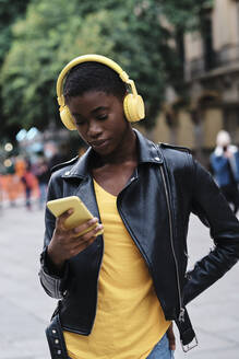 Young woman wearing headphones using smart phone while standing with hand on hip in city - AGOF00026