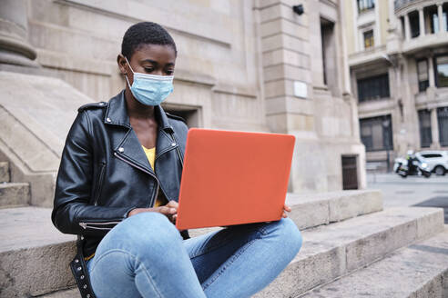 Young woman wearing protective face mask using laptop while sitting on steps in city - AGOF00032