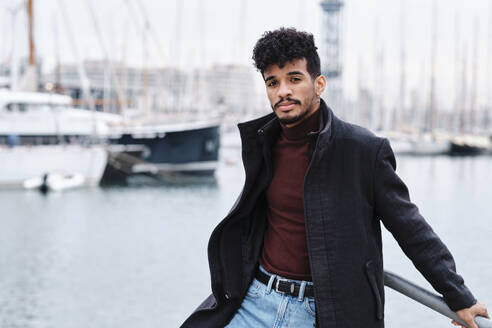 Young fashionable man wearing jacket while leaning on railing at harbor - AGOF00038