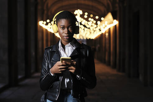 Young woman with headphones and mobile phone staring while standing at corridor - AGOF00041