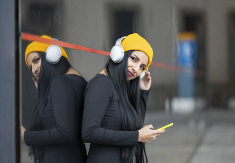Young woman with headphones holding smart phone against glass wall - JCCMF01200
