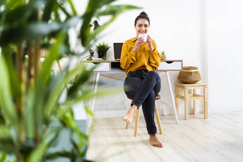 Young woman smiling while drinking coffee sitting on stool at home - GIOF11016