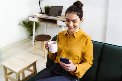Smiling young woman drinking coffee while using mobile phone sitting at home - GIOF11022