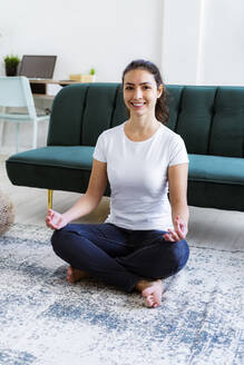 Smiling woman doing yoga while sitting on floor at home - GIOF11052