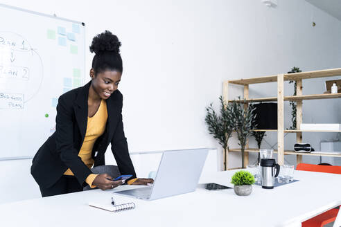 Smiling young Afro businesswoman using smart phone while looking at laptop in office - GIOF11123