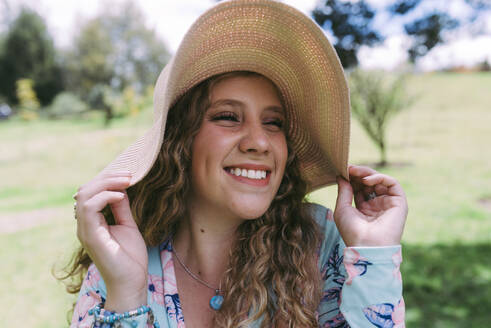 Smiling young woman wearing sun hat at public park during sunny day - DSIF00315