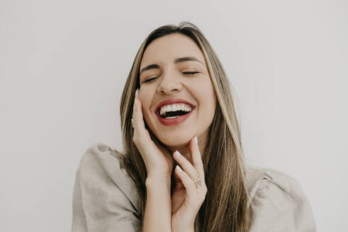 Laughing woman touching cheek with eyes closed against white background - DSIF00335