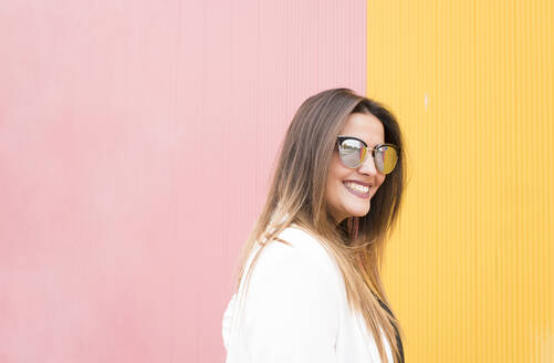 Beautiful woman in sunglasses against pink and yellow wall - DAMF00703