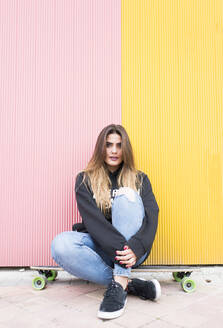Young woman sitting on skateboard against pink and yellow wall - DAMF00709
