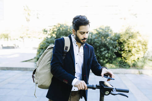 Mid adult businessman with backpack using mobile phone while standing by bicycle - XLGF01163