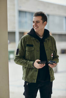 Smiling handsome man with mobile phone holding credit card while looking away - ACPF01113