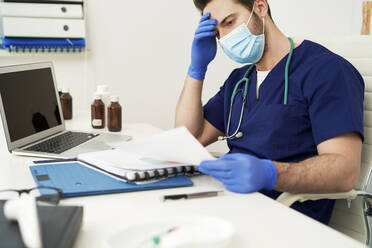Tired male doctor sitting at desk while looking at documents - ABIF01334