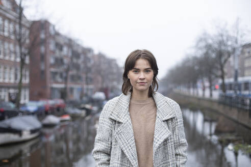 Female in warm clothing standing by canal against sky - AXHF00166