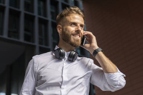 Businessman looking away while talking on mobile phone outdoors - BOYF01776