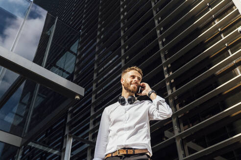 Businessman talking on mobile phone while standing against building - BOYF01782
