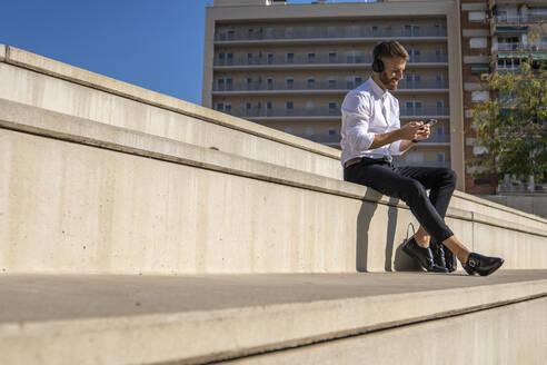 Businessman wearing headphones using smart phone while sitting on steps - BOYF01809