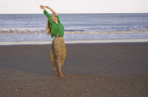 Carefree woman dancing on beach against sky - AZF00193