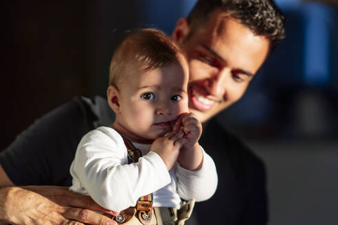 Smiling father holding cute baby boy while standing at home - PGF00437