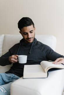 Young man with coffee cup reading book while sitting on sofa at home - EGAF01732