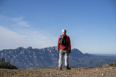 Senior hiker with backpack admiring Montserrat view while standing on mountain at Sant Llorenc del Munt i l'Obac, Catalonia, Spain - AFVF08155
