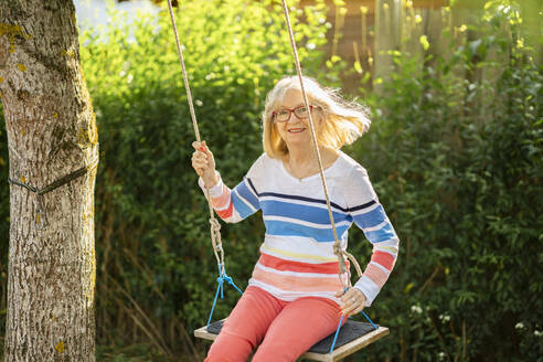 Cheerful senior woman swinging in garden - AKLF00037