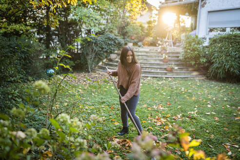 Happy woman sweeping garden with broom in back yard - AKLF00052