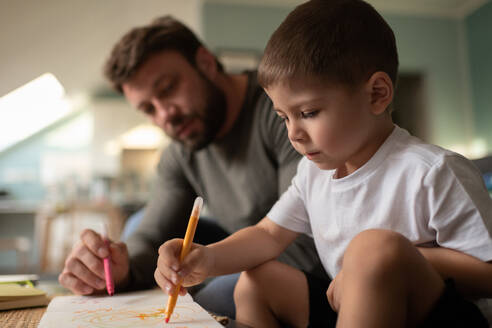 Focused boy drawing with father - CAVF93376