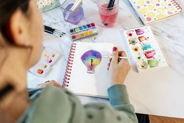 Woman painting light bulb with watercolors on spiral notebook - GEMF04670