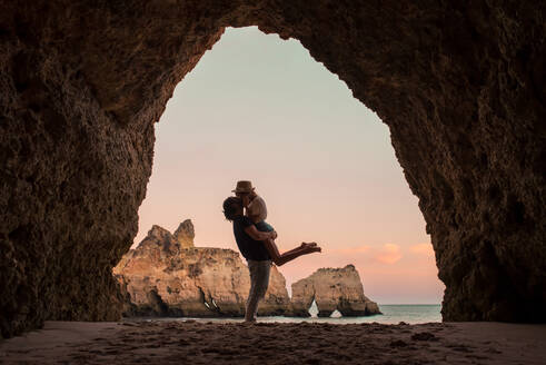 Full body side view unrecognizable man lifting and kissing girlfriend while standing in entrance of cave near sea in Benagil caves in Algarve, Portugal - ADSF20871