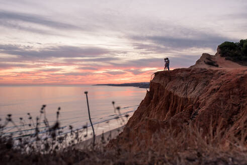 Side view of unrecognizable coupe standing together in mountain cliff in the coastline during beautiful sunset in Tavira in Algarve, Portugal - ADSF20895